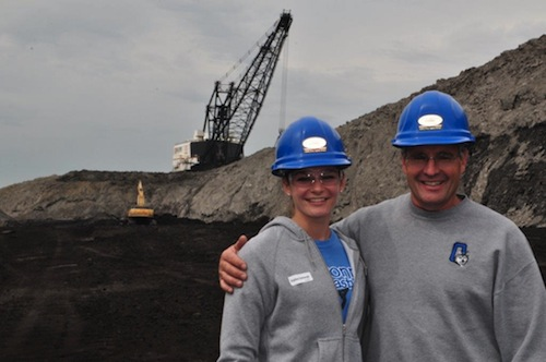 two tour group members in front of excavator